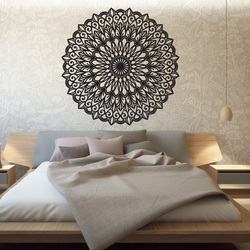 Carved flower mandala wooden picture on a plywood wall